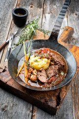 Traditionelle deutsche geschmorte Schweinebäckchen in brauner Rotwein Sauce mit Kartoffel Püree und Pilzen als closeup in einer schmiedeeisernen Pfanne
