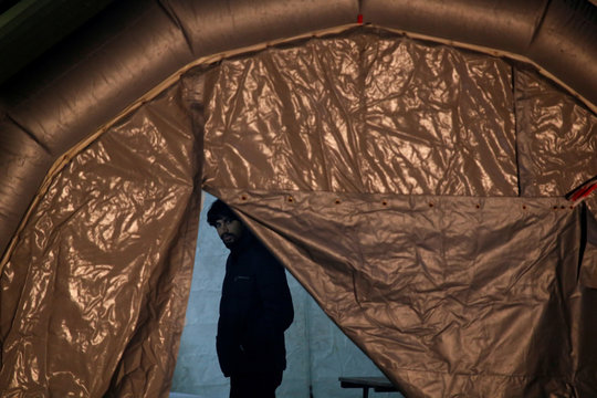 A migrant, part of a group of 69 migrants rescued 117 nautical miles south west of Malta by the Armed Forces of Malta (AFM), waits to be processed after arriving at the AFM Maritime Squadron base in Valletta's Marsamxett Harbour