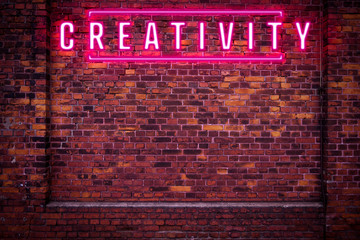 Magenta creativity neon sign on red brick wall