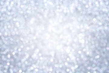High resolution silver colored blurred bokeh background. Abstract full frame shiny glitter background for Christmas, New Year, holiday season and celebration. Vignetting and brighter in the middle.