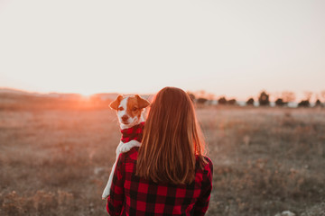 woman and dog at sunset wearing same plaid shirt and bandana. outdoors
