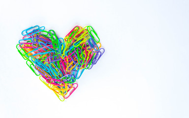 Paper clips lined in heart shape on white background