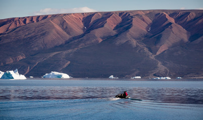 Photo sur Aluminium zodiac driving through arctic landscape with high fjords and floating icebergs