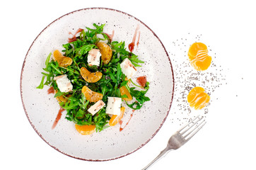 Delicious fruit and vegetables salad. Tangerine, feta cheese, arugula and chia seeds in plate. Healthy food concept