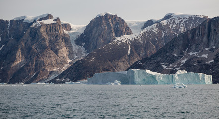 arctic landscape with icebergs among east Greenland fjords