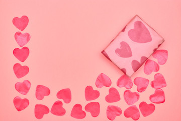 Gift in Kraft paper with red hearts on pink background with hearts. The Concept Of Valentine's Day. view from above . copy space.