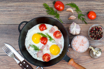Frying pan with fried eggs, bacon and tomatoes
