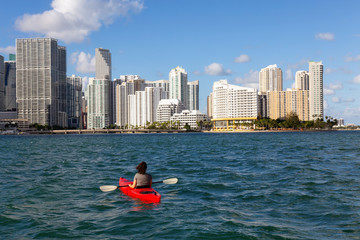 Adventurous girl kayaking in front of a modern Downtown Cityscape during a sunny evening. Taken in Miami, Florida, United States of America.