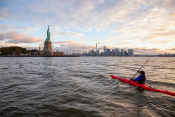 Adventurous Girl Sea Kayaking near the Statue of Liberty during a vibrant cloudy sunrise. Taken in...