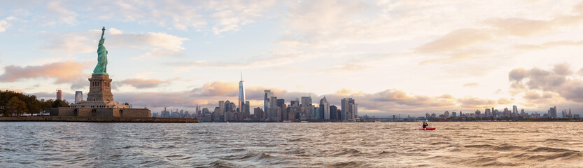 Panoramic view of the Statue of Liberty and Downtown Manhattan in the background during a vibrant cloudy sunrise. Taken in Jersey City, New Jersey, United States.