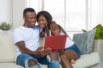 happy beautiful black African American couple in love enjoying at living room sofa couch with laptop computer having fun with internet  networking together at modern apartment