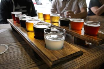 Twelve Beer Samples Being Shared at a Table Fotobehang