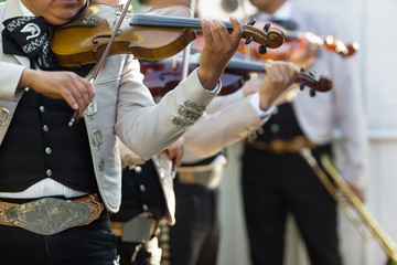 Mexican mariachi with white traditional costumes playing the violins at a party