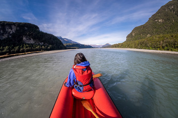 Young girl kayaking down a dart river of New Zealand. Girl traveling down river stream. Woman enjoying scenery. Lifestyle, adventure and exploration concept image. Recreation leisure activity