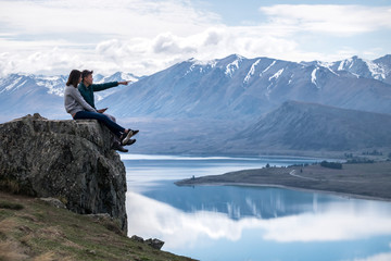 Couple enjoys beautiful scenery in New Zealand. Romantic couple smiling. A pair of couple goes on honeymoon in natural landscape. Leisure image of a young couple in happiness. Happy people on holiday.