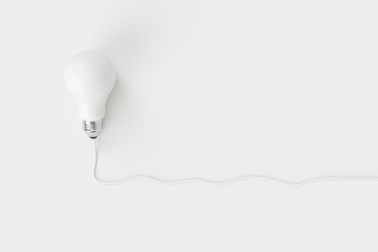 Minimal concept. outstanding white light bulb with cable on white background for copy space.
