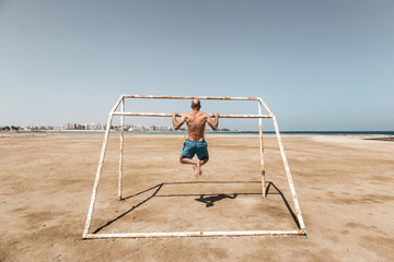 Man doing pull-ups on the beach