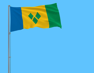 Isolate flag of Saint Vincent and the Grenadines on a flagpole fluttering in the wind on a blue