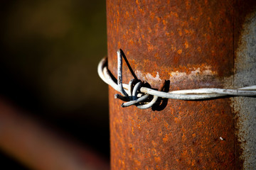 Barbed wired fence secured to post providing security to farmland in rural Hampshire