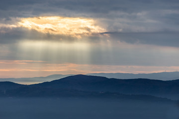 Sunray shines through clouds over the mountains and a sea of fog