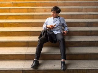 Businessman sitting in outdoors park and stressed because of business work failure