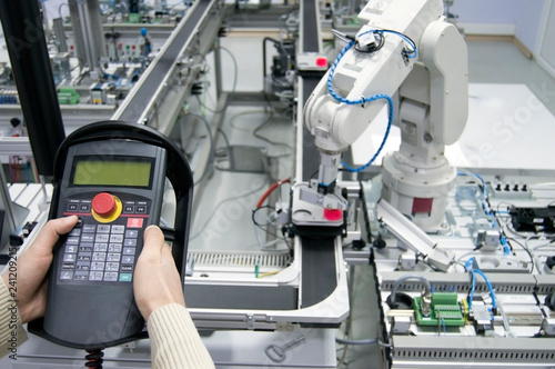 Man is holding teach panel (tablet) to control a robotic arm which