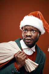 Modern Santa Claus. Scared man posing in green coat and red sweater, with santa hat and bag. Studio shot, brown background