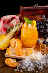 Vertical image of glass of citrus homemade orange lemonade at decorated with fruits and ice wooden table background.