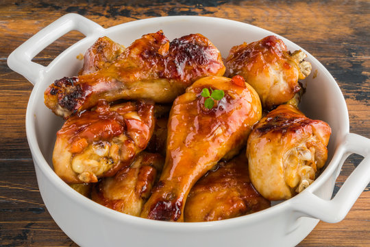 Baked glazed chicken drumsticks. Marinated in teriyaki, apricot jam, wine vinegar and corn starch sauce. White saucepan on  wooden rustic table