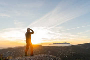 Anonymous man standing in cliff during sunset
