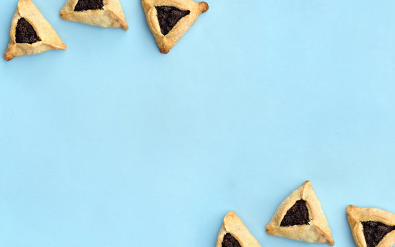 Triangular cookies with poppy seeds ( hamantasch or aman ears ) for jewish holiday of purim celebration on blue paper background with space for text. Top view, flat lay