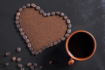 Heart of beans and brown cup of coffee