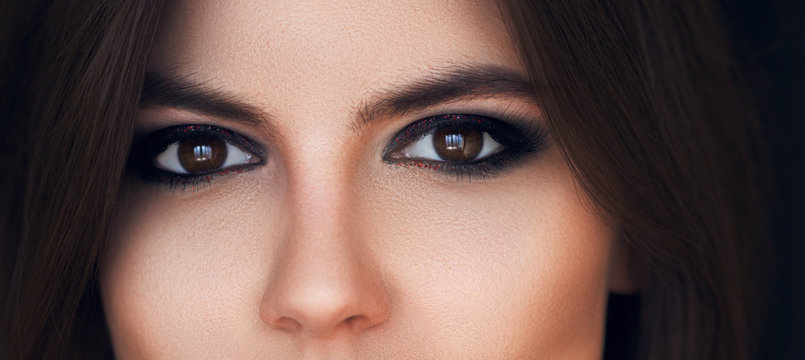 Beautiful eyes with bright makeup. Sexy view, sensual look. Female eyes with long eyelashes. Smoky eye makeup. Eyeshadows. Perfect eyebrows and long lashes. Cosmetics and make-up. Beauty concept