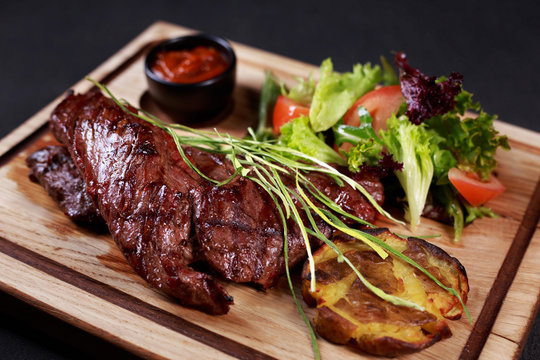 grill and barbeque, meat restaurant menu, skirt steak, beefsteak served with vegetable salad and potatoes on board, traditional american cuisine