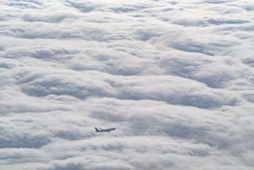 a commercial jet airplane flying above the clouds