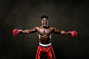 Muscular African American Black male sweaty boxer does an aggressive scream with arms open looking at camera with dramatic lighting with a black background
