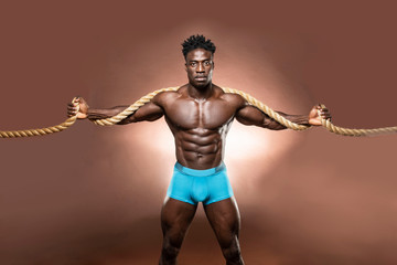 Muscular African American Black athletic fitness model wearing blue underwear  holding a thick rope with six pack abs in studio with dramatic lighting against a brown background