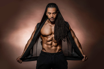 Muscular African American Black athletic fitness model wearing  black hoodie with six pack abs in studio with dramatic lighting against a brown background