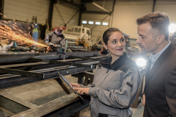 Happy female factory worker shows her tablet to her boss