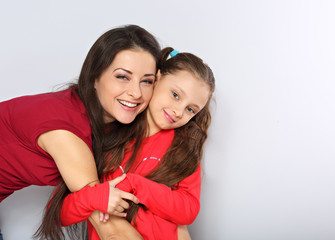 Mother and kid girl hugging with happy emotional faces on blue background with empty copy space