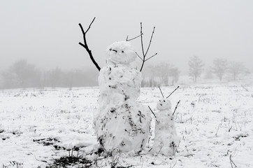 creepy snowmen from dirty snow on the background of trees and fog