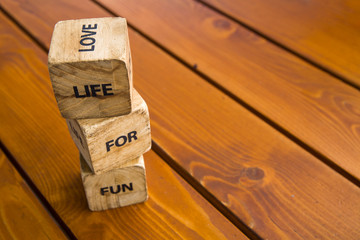 Wooden blocks with the words lie on the table. Wooden cubes with letters and symbols. Life for love.