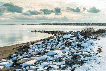 Snow-covered rocks along beach on Narrangansett Bay