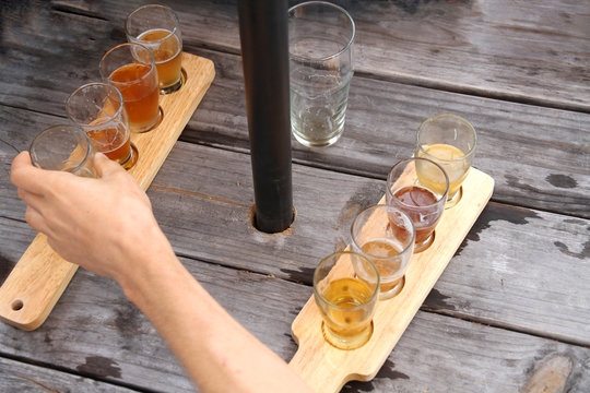 Hand Reaching for a Beer on Picnic Table