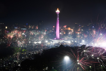 Fireworks explode around National Monument during New Year's Eve celebration in Jakarta