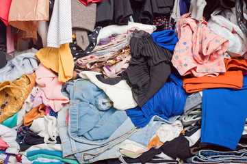 Pile of messy clothes in closet. Untidy cluttered woman.