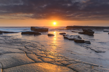 An Atmospheric Sunrise Seascape and Rock Surface