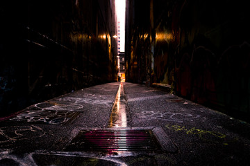 Abstract style photograph looking down a graffiti lined alley way.