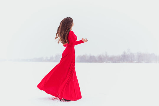 Hispanic woman dancing in silk dress at snowy day, artistic red flowing gown waving and fluttering fabric, Passion concept