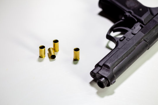 Handgun with 9mm shell casings on white table